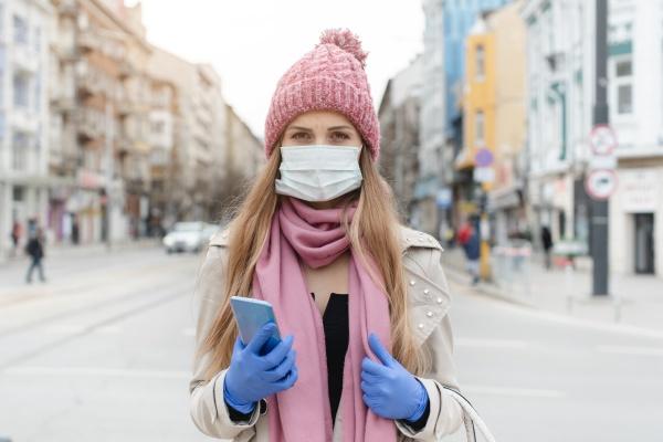 besorgte frau die mit medizinischer maske