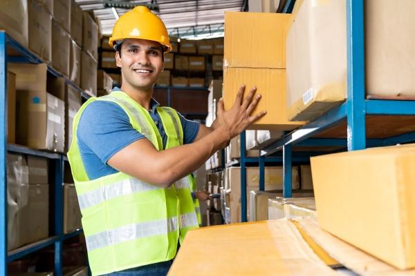 indischer lagerarbeiter legt karton ins regal