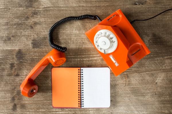 altes orangefarbenes telefon und leeres notizbuch