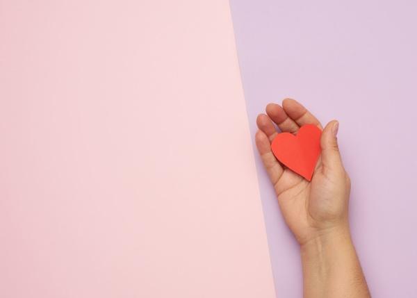 weibliche hand haelt rotes papierherz auf