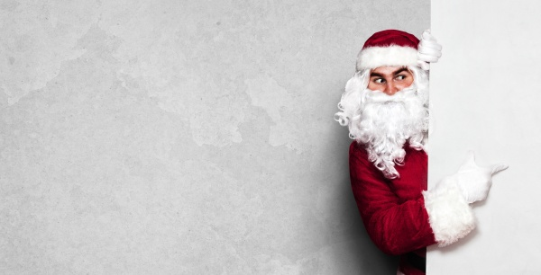 gluecklicher weihnachtsmann zeigt in leere wand