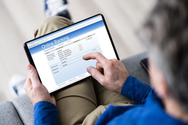 mann mit tablet computer UEberpruefung bankauszug