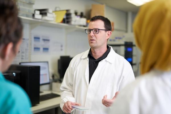 maennlicher wissenschaftler im laborgespraech mit kollegen