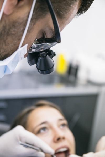 maennlicher zahnarzt in chirurgischen lupen untersuchung