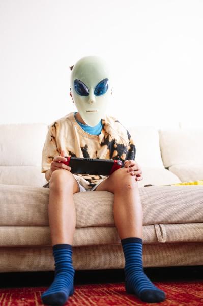 junge traegt alien maske spielen handheld
