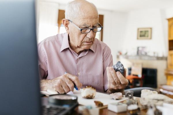 AElterer mann analysiert mineralien und fossilien