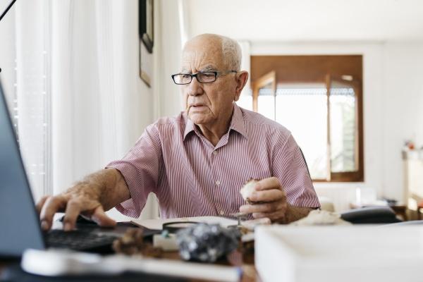 rentner aelterer mann mit laptop waehrend