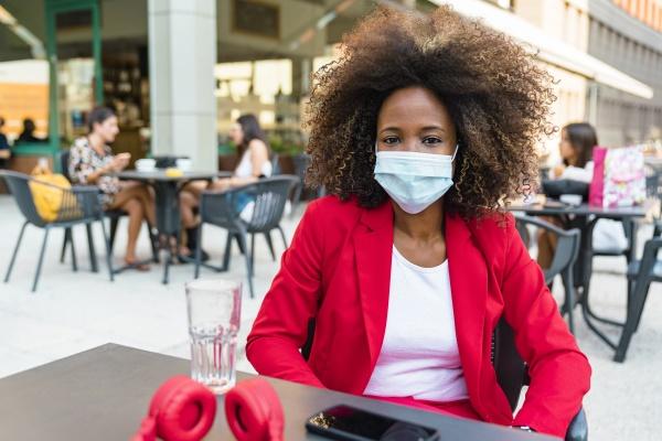 frau mit schutzmaske im strassencafe