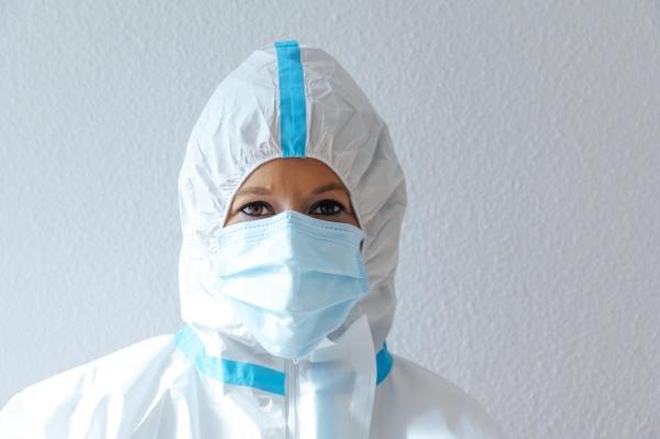 krankenschwester traegt schutzanzug und arbeitskleidung waehrend