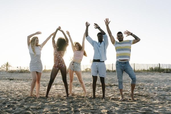 freunde mit erhobener hand am strand
