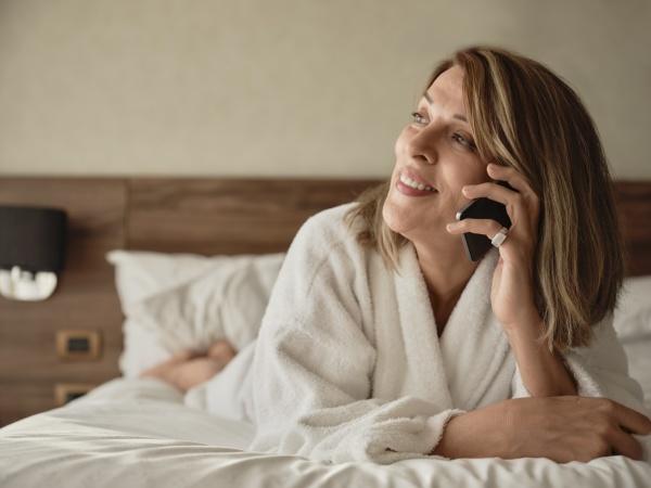 laechelnde seniorin die am telefon spricht