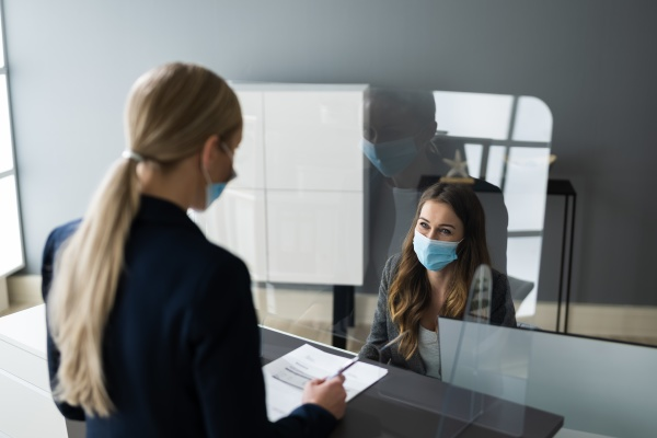 hotel rezeption geschuetzt durch medizinische maske