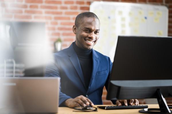 gluecklicher professioneller afrikanischer mitarbeiter