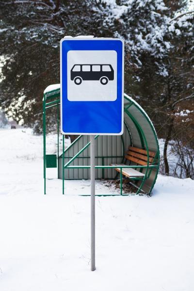 bushaltestelle mitten in einer schoenen winterstrasse