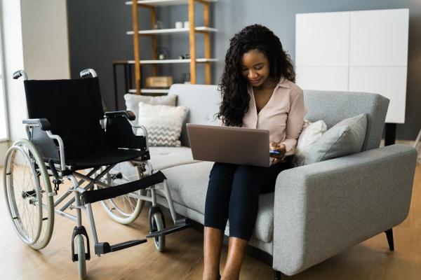 afrikanische frau zu hause mit computer