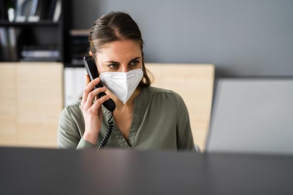 rezeptionist am telefon tragen gesichtsmaske