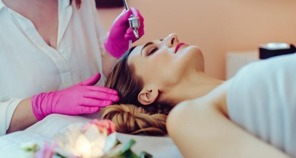 kosmetologe gibt frau eine hautbehandlung mit