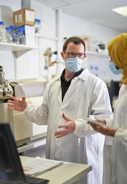 wissenschaftler in gesichtsmasken sprechen im labor
