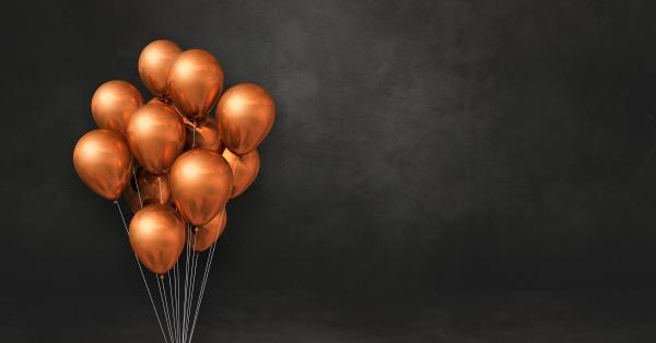 kupferballons buendeln sich auf einem schwarzen