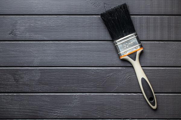 pinsel auf schwarzem plankenhintergrund malen