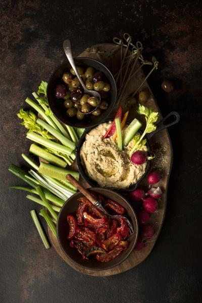 weideplatte mit hummus oliven sonnengetrockneten tomaten