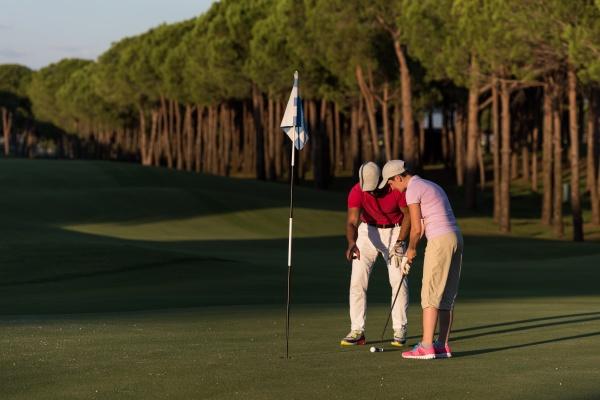 maennlicher golflehrer unterrichtet golfspielerin personal trainer