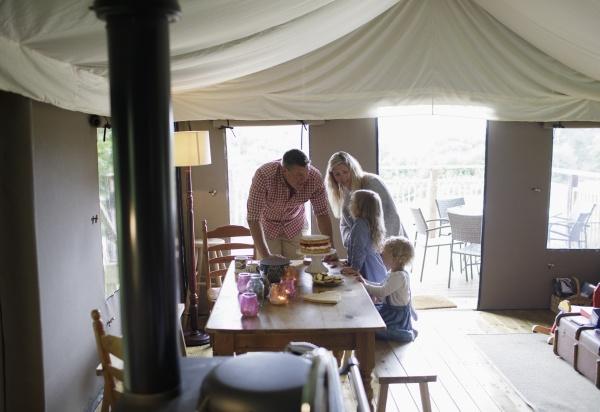 glueckliche familie am esstisch mit erdbeerkuchen