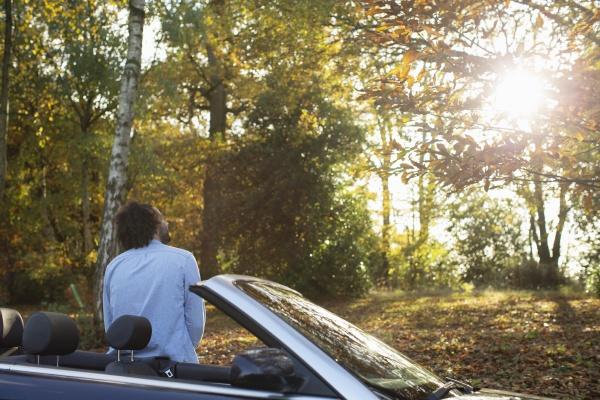 mann bei cabrio ins sonnigem herbstpark