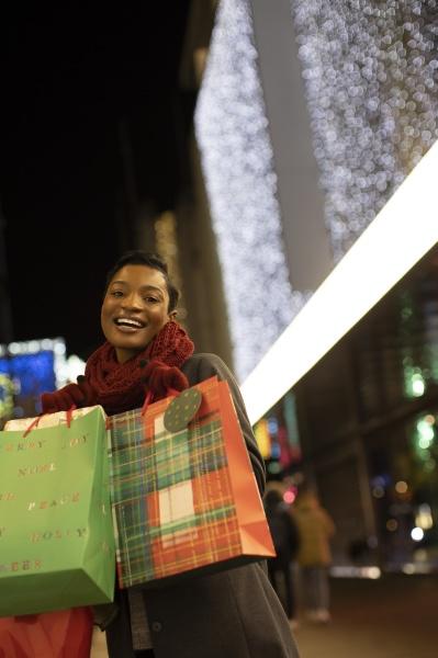 portraet glueckliche junge frau mit weihnachtseinkaufstaschen