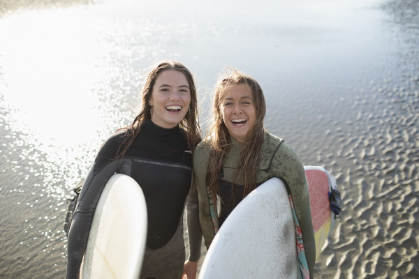 portraet glueckliche junge surferinnen mit surfbrettern