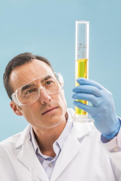 wissenschaftler betrachtet gelbe fluessigkeit im messbecherglas