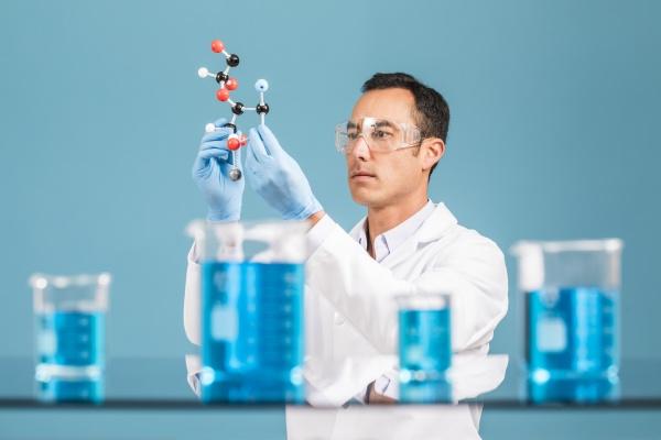 wissenschaftler haelt molekuelmodell blaue fluessigkeit in