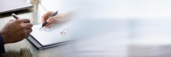 geschaeftsmann unterzeichnet vertrag mit schluesseln