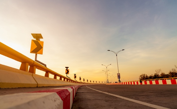 kurvenbetonstrasse mit kurvenverkehrszeichen und rot weissem