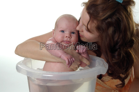 mother is kissing baby while bathing