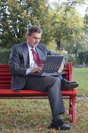 geschaeftsmann mit laptop auf parkbank
