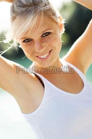 smiling woman with hands on head