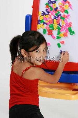 junges maedchen spielt mit buchstaben