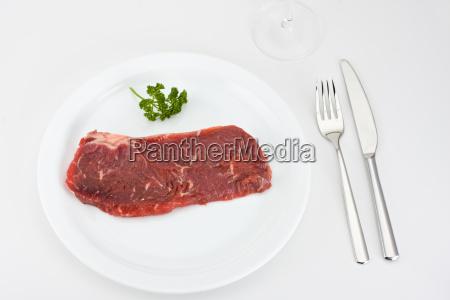 raw steak on a white plate