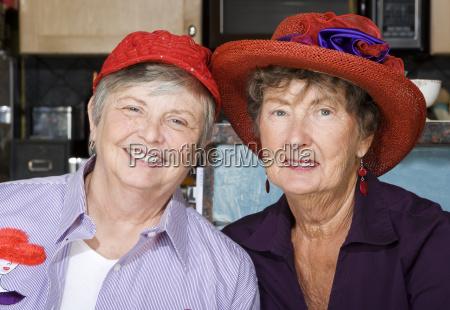 two senior women wearing red hats