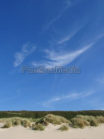 blauer himmel ueber duenenlandschaft