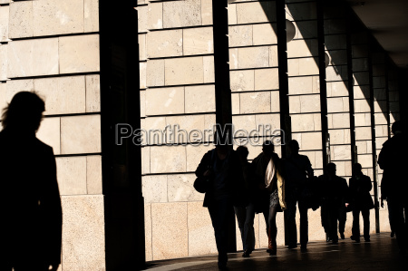 silhouettes of people between arcades