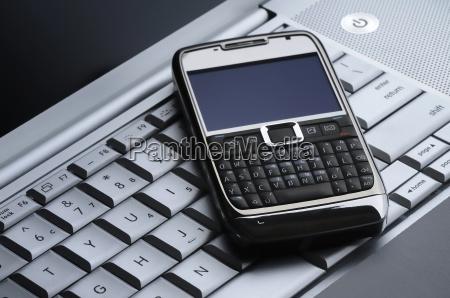 smart handy auf einem silbernen laptop