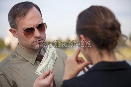 mann bietet geld einer frau an