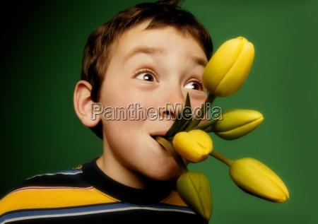 junge mit blumen in seinem mund