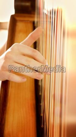 finger zupfen auf saiten einer harfe
