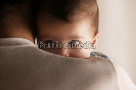 baby peering ueber papas schulter