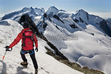 mountaineer walks down along a snowy