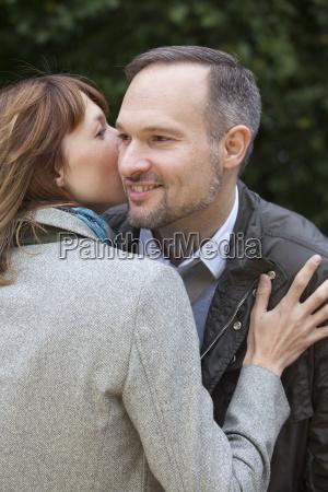 woman kisses man while meeting