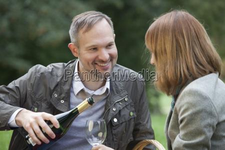 man pours champagne